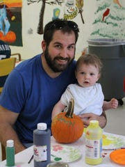 Mathew McCloskey and his 15-month-old daughter, Davin, visit the Hammonton Family Success Center on Friday for a pumpkin decorating activity.