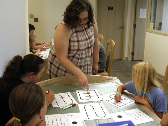 Sheila Olson teaches kids about coding during a STEM