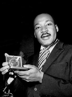 In this Dec. 10, 1964, photo, the Rev. Martin Luther King Jr. holds his 1964 Nobel Peace Prize medal in Oslo, Norway. King was honored for promoting the principle of nonviolence in the civil rights movement.
