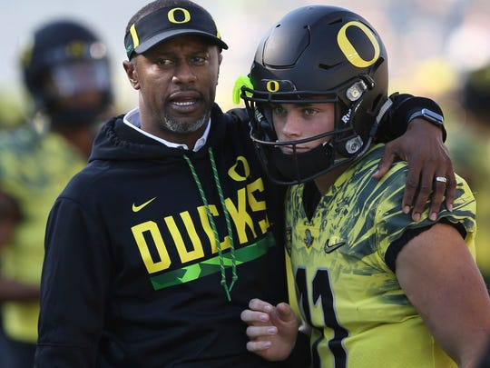 Oregon head coach Willie Taggart, left, offers encouragement to his quarterback Braxton Burmeister before the start of the NCAA college football game game against Utah Saturday, Oct. 28, 2017, in Eugene, Ore. (AP Photo/Chris Pietsch)