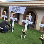 Sonja Haller/the RepublicA member of St. Mark Coptic Orthodox Church in Scottsdale lights a candle Sunday at the base of a cross to honor one of 21 Egyptian Christians shown beheaded by members of ISIS.