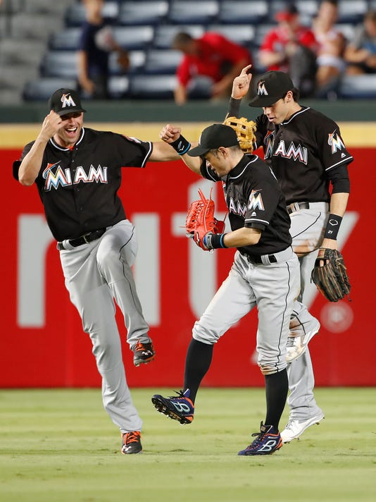 Miami Marlins outfielders from left; Jeff Francoeur, Ichiro Suzuki, and Christian Yelich celebrate after defeating the Atlanta Braves 7-5 in a baseball game, Tuesday, Sept. 13, 2016, in Atlanta. (AP Photo/John Bazemore)
