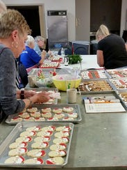 Cookies are prepared in a team setting with volunteers