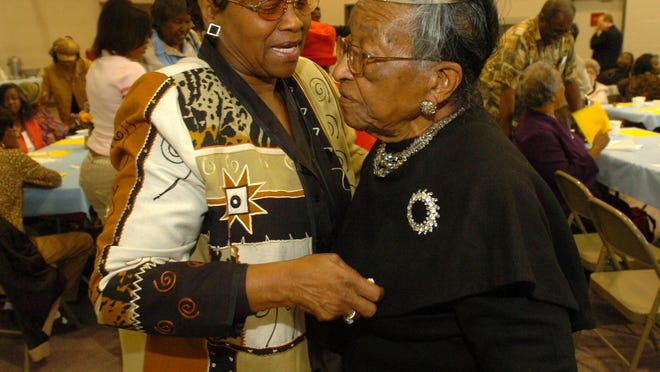 Surpiner Benjamin, left, greets Lizzie Johnson at a celebration for Johnson's 100th birthday at the Salvation Army on East Stoner Avenue in january 2007. Johnson died last week at age 108.