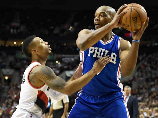Portland Trail Blazers guard Damian Lillard, left, defends as Philadelphia 76ers forward Carl Landry looks for an opening during the first quarter of an NBA basketball game in Portland, Ore., Saturday, March 26, 2016. (AP Photo/Steve Dykes)