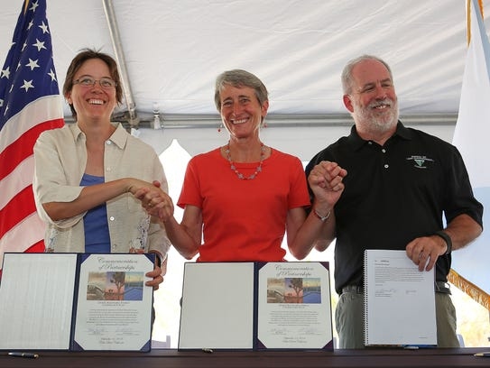From left, California Energy Commissioner Karen Douglas, then-Interior Secretary Sally Jewell and California BLM Director Jerry Perez celebrate the signing of the Desert Renewable Energy Conservation Plan on Sept. 14, 2016 at the Santa Rosa and San Jacinto Mountains National Monument Visitor Center in Palm Desert.