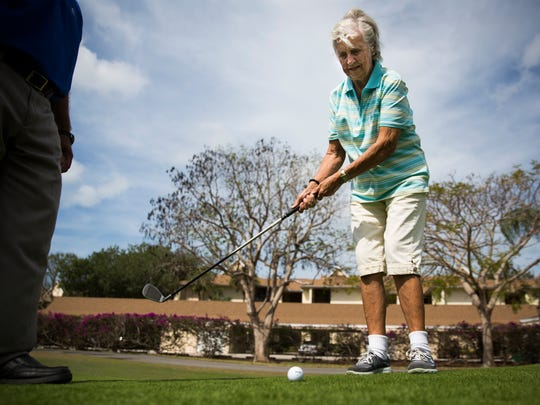 Shirley Harmann, 87, practices her chipping with Stan Geer, the community's golf pro, on Wednesday, April 19, 2017 at Vi at Bentley Village in North Naples. Harmann plays every week and is chairperson of the Nine-Hole Club at her senior community.
