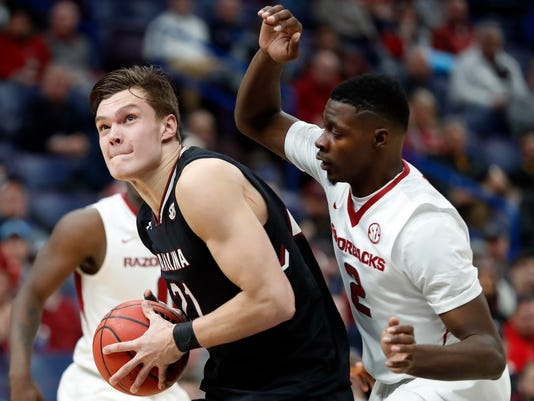 South Carolina's Maik Kotsar, left, heads to the basket as Arkansas' Adrio Bailey defends during the second half in an NCAA college basketball game at the Southeastern Conference men's Thursday, March 8, 2018, in St. Louis. Arkansas won 69-64. (AP Photo/Jeff Roberson)