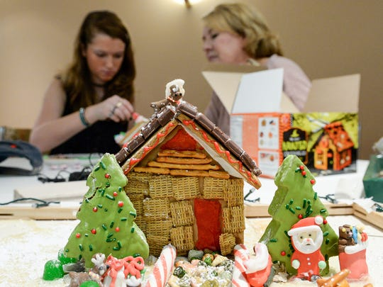 Volunteer mentor Libba Kellner, right, of Anderson watches Raven Huckabaa of Anderson decorate a gingerbread house during the Big Brother Big Sisters of the Upstate event at the Anderson County Museum in Anderson on Tuesday.
