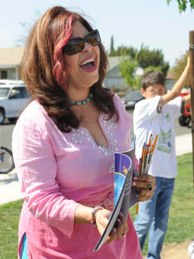 "Aracely Alvarado of Dinuba laughs as she tells her story ""Subiendo a la Luna"" about going up to the moon at a children's festival in April put on by Campesinas Unidas del Valle de San Joaquin at Mulcahy Park in Tulare."