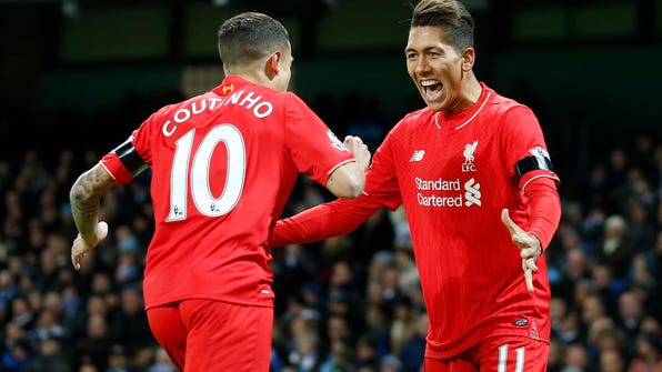 Liverpool's Roberto Firmino celebrates with teammate Liverpool's Philippe Coutinho after his cross which is then turned in by Manchester City's Eliaquim Mangala who scores an own goal for the opening goal of the game during the English Premier League soccer match between Manchester City and Liverpool at the Etihad Stadium, Manchester, England, Saturday, Nov. 21, 2015. (AP Photo/Jon Super)