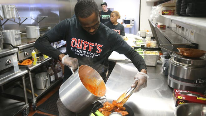 Nicklon Wilson plates an order of Duff's Famous Wings at it's newest location on West Henrietta Road.