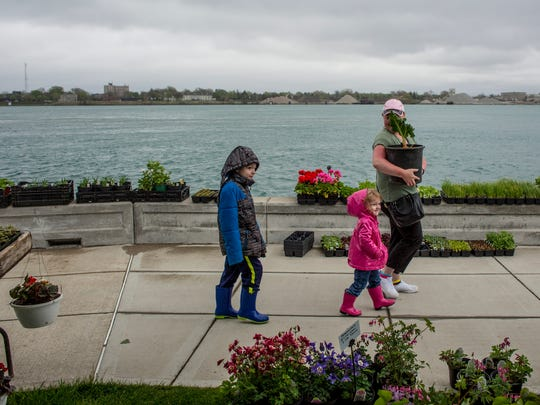 Kim Kendrick, of Goodells, holds a rhubarb plant while walking with her children Ben, 7, and Haylee, 2, Saturday, May 14, 2016 at the Vantage Point Farmers Market in Port Huron.