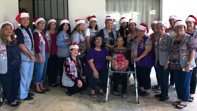 Sunshine Lions Club members visited Mrs. Ester Lizama, 84, at her home in Agana Heights on Dec.  9. The Lions brought a fruit basket, song, and cheer to the elderly resident. Pictured front left: Lion Marietta Camacho, Barbara Jose, and Lizama. Standing from left: Lions Lou Jean Borja, Pete Babauta, Dee Cruz, Dot Leon Guerrero, Connie Rivera, Clarice Quichocho, Annie Artero, Mary Torres, Julie Garcia, Rosie Matsunaga, Ewy Taitano, Helen Colby, Jovie Mejorada, Tish Tano, Jill Pangelinan, and Julie Cruz.