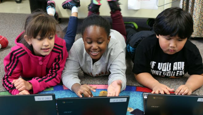 Second-graders Ruby Castro, Heaven Sims and Daniel Go work on laptops and use Java Script to write code Wednesday during a class on coding at Brookside Elementary School in Ossining.