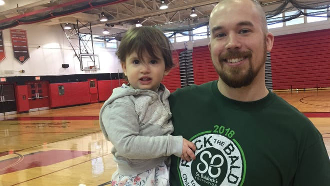 Woodbridge High School teacher Brian O'Halloran with daughter Teagan after he shaved his head Saturday to support St. Baldrick's Foundation