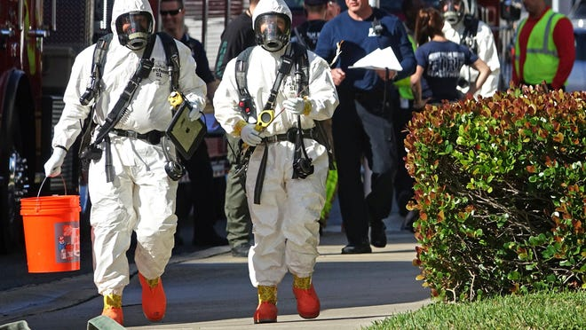 West Palm Beach Fire Rescue members in hazmat suits enter the Palm Beach County Courthouse Thursday morning, Jan. 23, 2020 to investigate a suspicious substance.