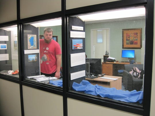 """Student Cooper Smith works on the exhibition """"The Tahoe Recreation Experience: Fun at the Lake"""" in the Mack Social Science building at the University of Nevada, Reno. The exhibit opens May 4, 2015."""