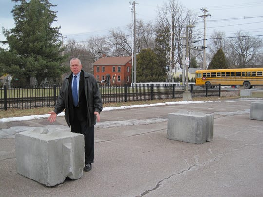 Gary von Stange, chairman of the Shelburne Selectboard, stands last week near cement blocks placed by Vermont Railway prohibiting access to the town's abandoned train station. The railroad removed the blocks this week after meeting with the town.