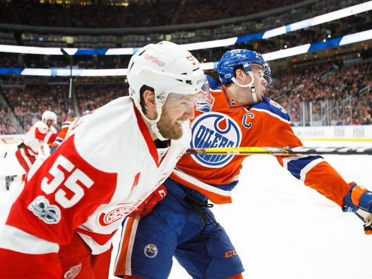 The Oilers' Connor McDavid battles Red Wings defenseman
