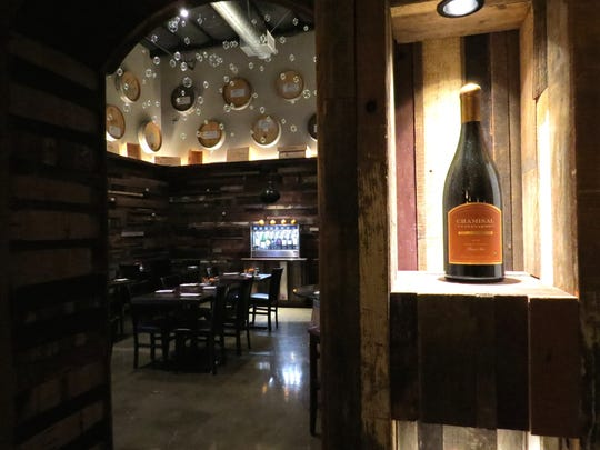 A bottle of Chamisal Vineyards pinot noir, right, is displayed next to the door leading to the Barrel Room at The Cave inside the Ventura Wine Co. The restaurant will offer Mother's Day brunch service on May 14.