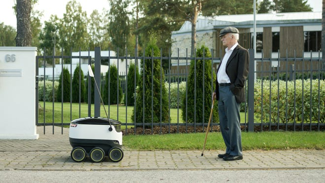 The Starship package delivery robot meets a pedestrian.