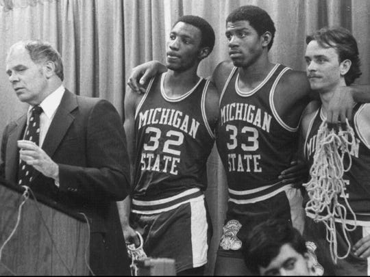 "FILE-Michigan State players Greg Kelser, left, Earvin ""Magic"" Johnson, center, and Terry Donnely listen to Michigan State coach Jud Heathcote during a news conference, in this MSU file photo. Heathcote's coaching career ended when the Spartans lost to Weber State 79-72 in the NCAA Southeast Regional tournament, Friday, March 17, 1995, in Tallahassee, Fla. Heathcote's 24-year coaching career, 19 at Michigan State, ended with a record of 340-220 at Michigan State and 420-273 overall, and one NCAA title in 1979. (AP Photo/Michigan State, file)___DT7"