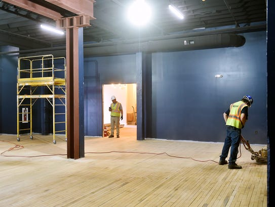 Workers prepare the new black box theater space at