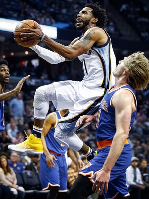 Memphis Grizzlies guard Mike Conley (middle) drives for a layup against the New York Knicks defenders Justin Holiday (left) and Ron Baker (right) during first quarter action at FedExForum on April 7, 2017.