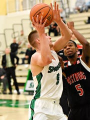 York College's Jared Wagner, left, takes the ball to the net while Frostburg's Lawrence Pettis defends during basketball action at Grumbacher Sport and Fitness Center on York College of Pennsylvania campus in Spring Garden Township, Wednesday, Dec. 6, 2017. York College would win 92-75.  Dawn J. Sagert photo