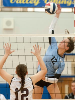 Mercy outside hitter Meridith Jewell smacks the ball toward Holy Cross opposite hitter Natalie Bodenbender. Mercy beat Holy Cross 3-0 to win the Sixth Region volleyball championship.