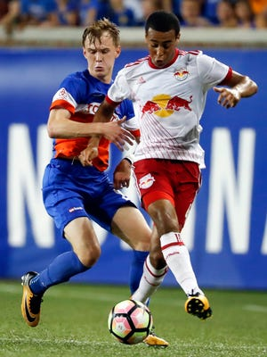 """FILE - In this Aug. 15, 2017, file photo ,New York Red Bulls midfielder Tyler Adams, right, shields for the ball against FC Cincinnati midfielder Jimmy McLaughlin, left, during the second half of a U.S. Open Cup semifinal soccer match in Cincinnati. Josh Sargent remembered when coach John Hackworth greeted the U.S. Under-17 team at breakfast in India last month and told players the American senior team had failed to qualify for next year's World Cup. """"Everybody thought he was joking,"""" Sargent said. In the wake of the failure, Sargent has been promoted to the national team along with Weston McKennie and Tyler Adams for Tuesday's exhibition at Portugal.  (AP Photo/John Minchillo, File)"""