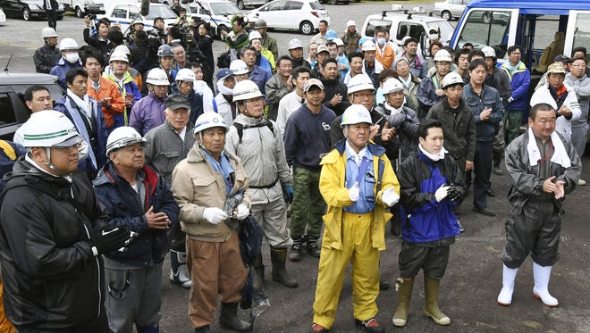Rescue workers celebrate after Yamato Tanooka, 7, was found near a military base after going nearly a week missing in a forest.