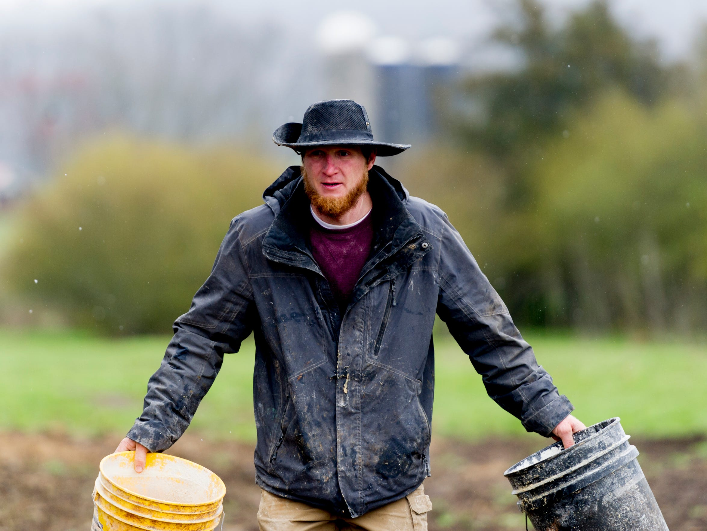 Caleb Watson carries buckets of feed to bring to his