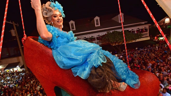"""""""Queen Sushi,"""" portrayed by female impersonator Gary Marion, sits in a giant replica of a woman's red high heel over Duval Street on Dec. 31, 2016, at the Bourbon St. Pub in Key West, Florida. The shoe drop is a Key West New Year's Eve tradition and is one of four Florida Keys warm-weather takeoffs on New York City's Times Square ball drop marking the arrival of the new year."""