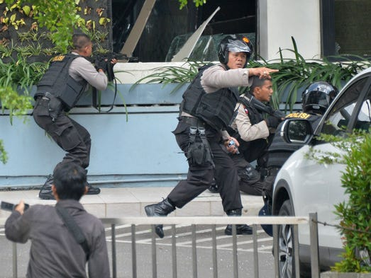 Indonesian police take position and aim their weapons
