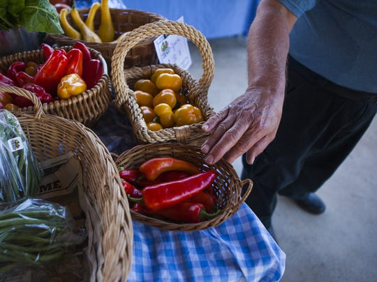 A farmer gestures to some of the sweet peppers at his booth while talking with a customer at the Waynesboro Farmers Market on Saturday, Aug. 22 2015.