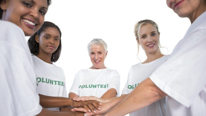 Team of female volunteers with hands together smiling