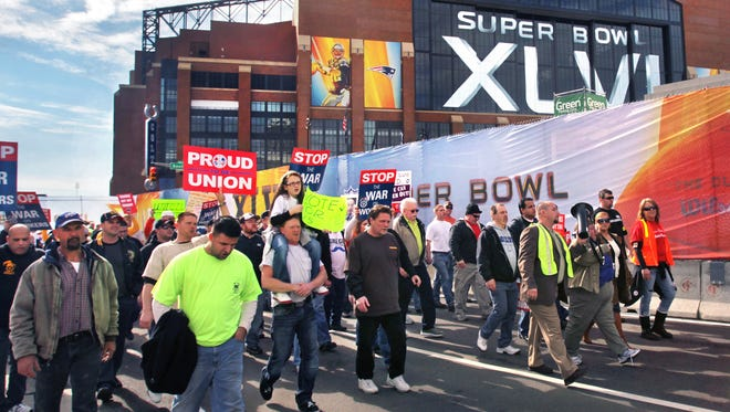 """Thousands of union workers marched past Lucas Oil Stadium in Indianapolis, site of Super Bowl XLVI between the New York Giants and the New England Patriots, on Feb. 1, 2012, in protest of the passage of """"right to work"""" legislation in the Indiana Senate."""