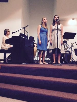 Kate Regan plays the piano while her daughters Erin Adams (left) and Alyssa Regan, right, sing at one of their concerts to benefit an anti-human trafficking organization.