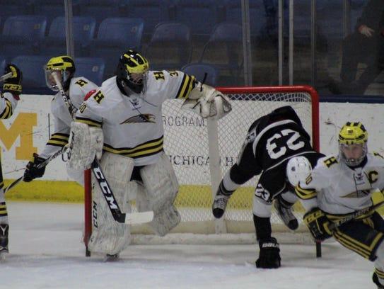 Hartland goalie Brett Tome sidesteps Nathan Nickelson