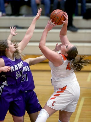 Central Kitsap post player MacKenzie Page takes a shot over North Thurston's Kortney Kerbaugh and Jane Kalama on Friday night at Central Kitsap.