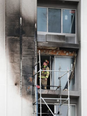 A firefighter inspects the charred outside wall of an upper level floor at the Holiday Inn Tuesday in Grand Chute.