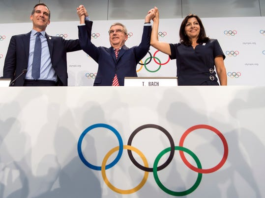 FILE - Int his July 11, 2017, file photo, from left, Mayor of Los Angeles Eric Garcetti, International Olympic Committee (IOC) President Thomas Bach, and Mayor of Paris Anne Hidalgo gesture during a press conference after the IOC Extraordinary Session at the SwissTech Convention Centre in Lausanne, Switzerland. One of the beautiful things about the Olympics is that some of the runners-up get prizes, too. Which brings us to Los Angeles. (Jean-Christophe Bott/Keystone via AP, File)
