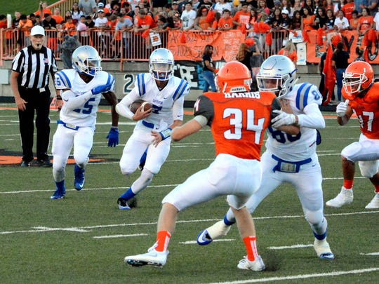 Carlsbad's Jonah Leyva bolts down the middle in the first quarter Friday at Artesia.