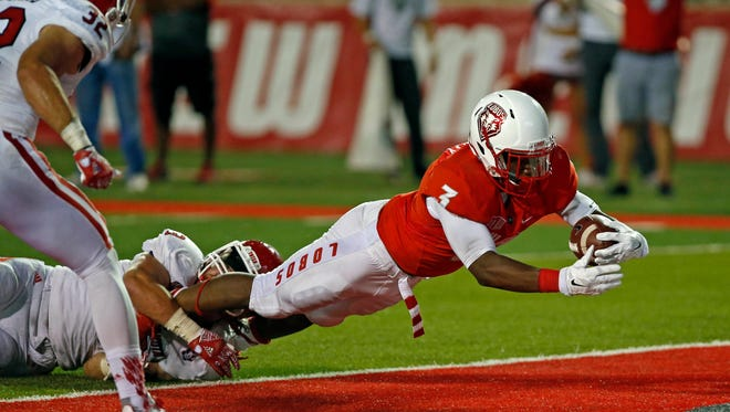 New Mexico running back Richard McQuarley (3) dives into the end zone to score against the defense of South Dakota Linebacker Jim Litrenta during the first half of an NCAA college football game in Albuquerque, N.M., Thursday, Sept. 1, 2016.