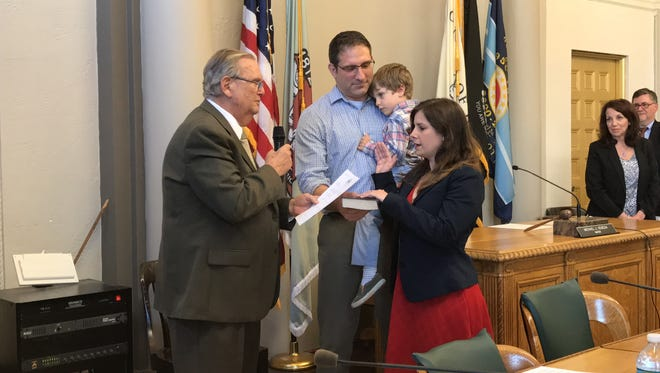 Assemblyman Ralph R. Caputo administers the oath of office to new Councilwoman Jenny Mundell while her husband, Abe, and son, Theodore, look on Wednesday, May 31, 2017.