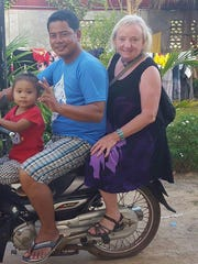 kao Virak, his daughter and Nancy Mitchell on a scooter before Mitchell realized her leg was broken.