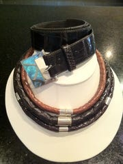 Alligator cord necklaces and belts accented with silver are shown.