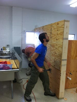 Workers construct parts of the kitchen and front room at Farmshed headquarters on Briggs Court in October.
